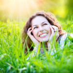 Lady smiling in grass.